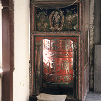 Nepal 2002 - The newly built Gompa in the town of Marpha, deep in the Kali Gandaki gorge in western Nepal, has a large prayer wheel in its entrance. Marpha and its neighbouring village of Tukuche are well know for their fruit liqueurs made from orchards introduced by the Swiss as part of a development program.